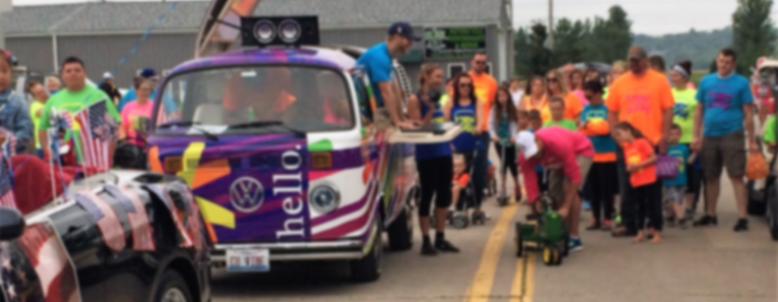 van in a parade with a group of people standing next to it and a man in a blue shirt leaning out the side